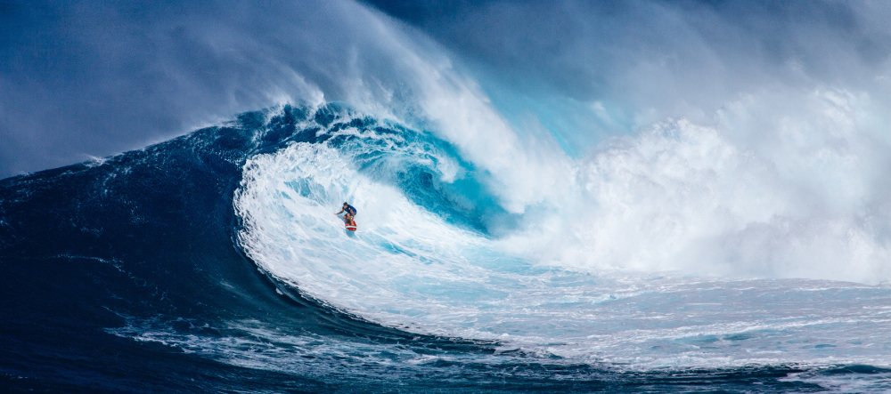 man surfing a big blue wave with an orange surf board, focus on the left of photo