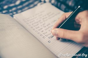 hand writing to do list with check marks on a notebook made of graph paper cross hatch