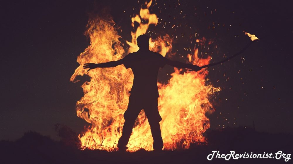 man standing in front of fire