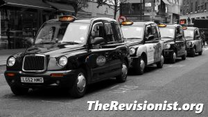 black taxi cabs lined up on the curb